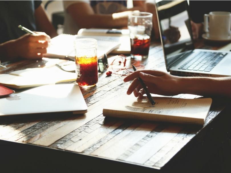 勉強会のテーブルでノートやパソコンを開いている様子の写真