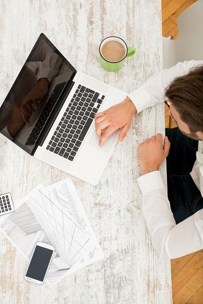 ノートパソコンを操作する男性を上から撮った写真