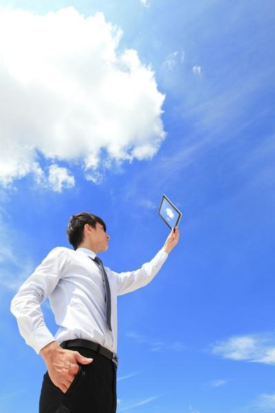 青空に雲の下で男性がタブレットを掲げている写真