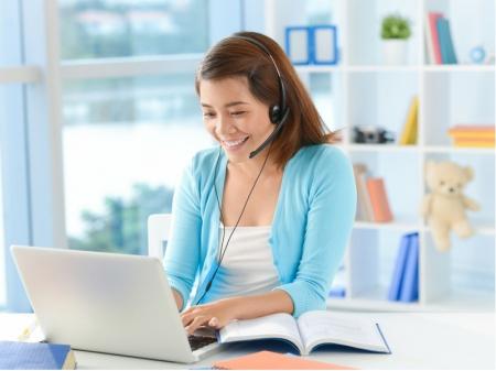 ヘッドセットを装着した女性がパソコンに向かって会話している様子