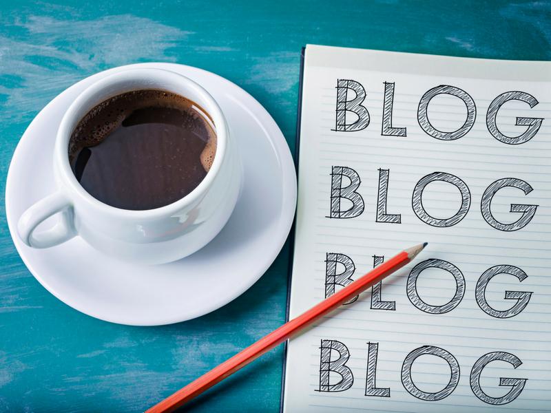 コーヒーとノートパッドと鉛筆が写った写真。ノートパッドには、ブログと書かれている。