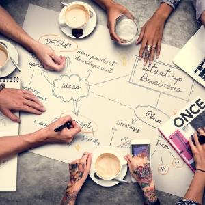 机上に広げたアイディア図とそれを取り囲む参加者の手が写った写真