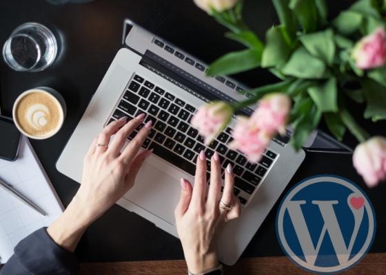 パソコンに入力する両手にワードプレスのロゴ