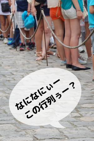 人の行列の足元の部分の写真に、「なに、なにぃー、この行列?」の文字