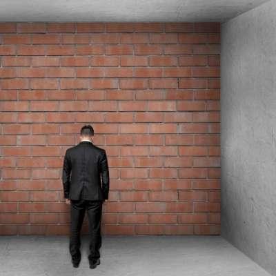 煉瓦の壁と向き合ってうつむく男性