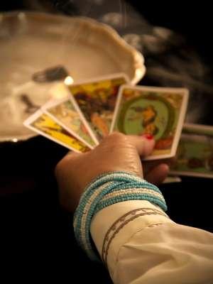 手に持たれた4枚のタロットカード