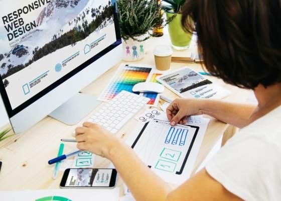 色見本などを見ながらデザインの作業をする女性